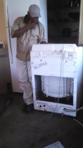 Zambian man fixes washing machine for OZ Kids International Orphanage.