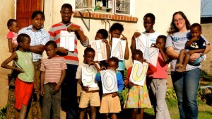 """Crystal with kids with signs that say """"Thank you"""" at an orphanage in Zambia."""