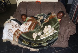 Lushomo and Chipego both sick together on the couch at Oz Kids Orphanage.