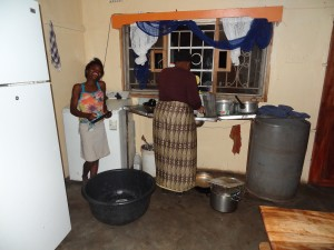 Mercy helping Auntie Royce with the dishes at Oz Kids Orphanage.