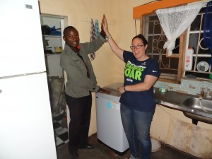 Crystal and manager Clyde with the new washing machine at an orphanage in Zambia.
